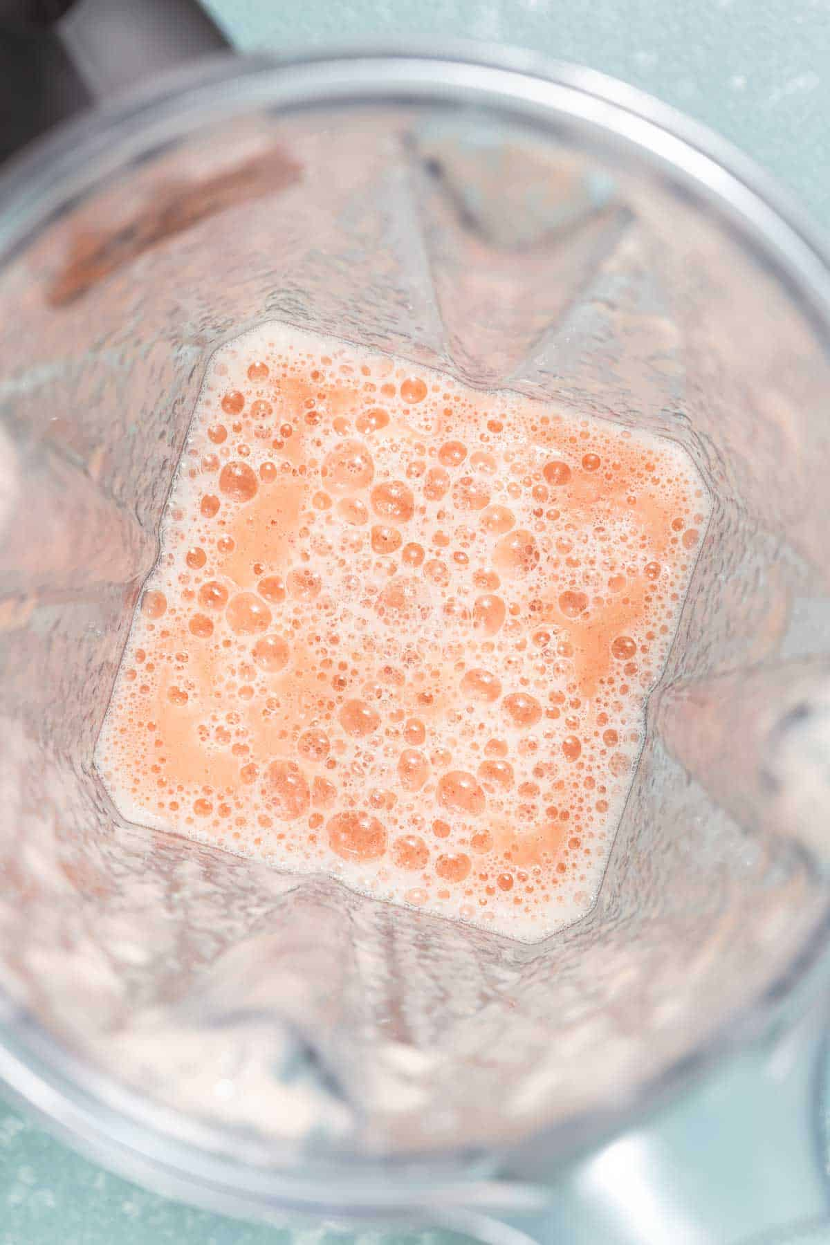 Overhead view of a blender with frothy orange liquid
