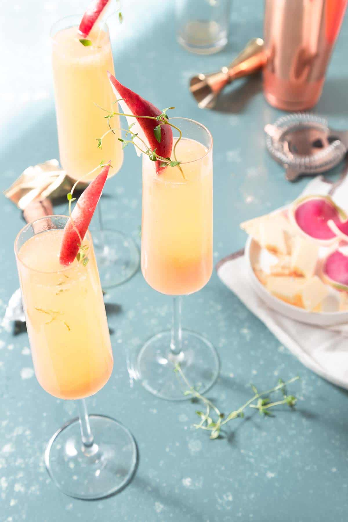 3 champagne flutes filled with a yellow drink and garnished with a slice of red pear