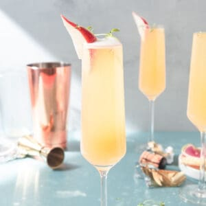 Champagne flutes filled with a yellow drink and garnished with a slice of red pear