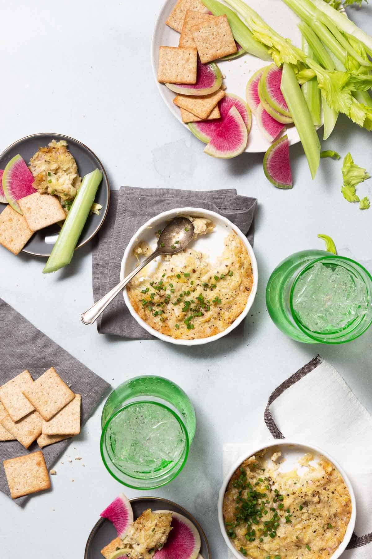 Two grey plates with dip and crackers. Two white bowls with baked artichoke dip.