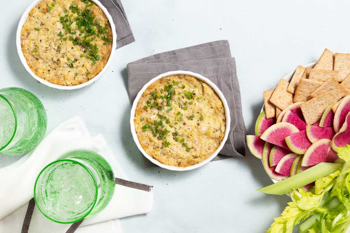 Overhead view of 2 white dishes with baked artichoke dip. Crackers and veggies on the side.