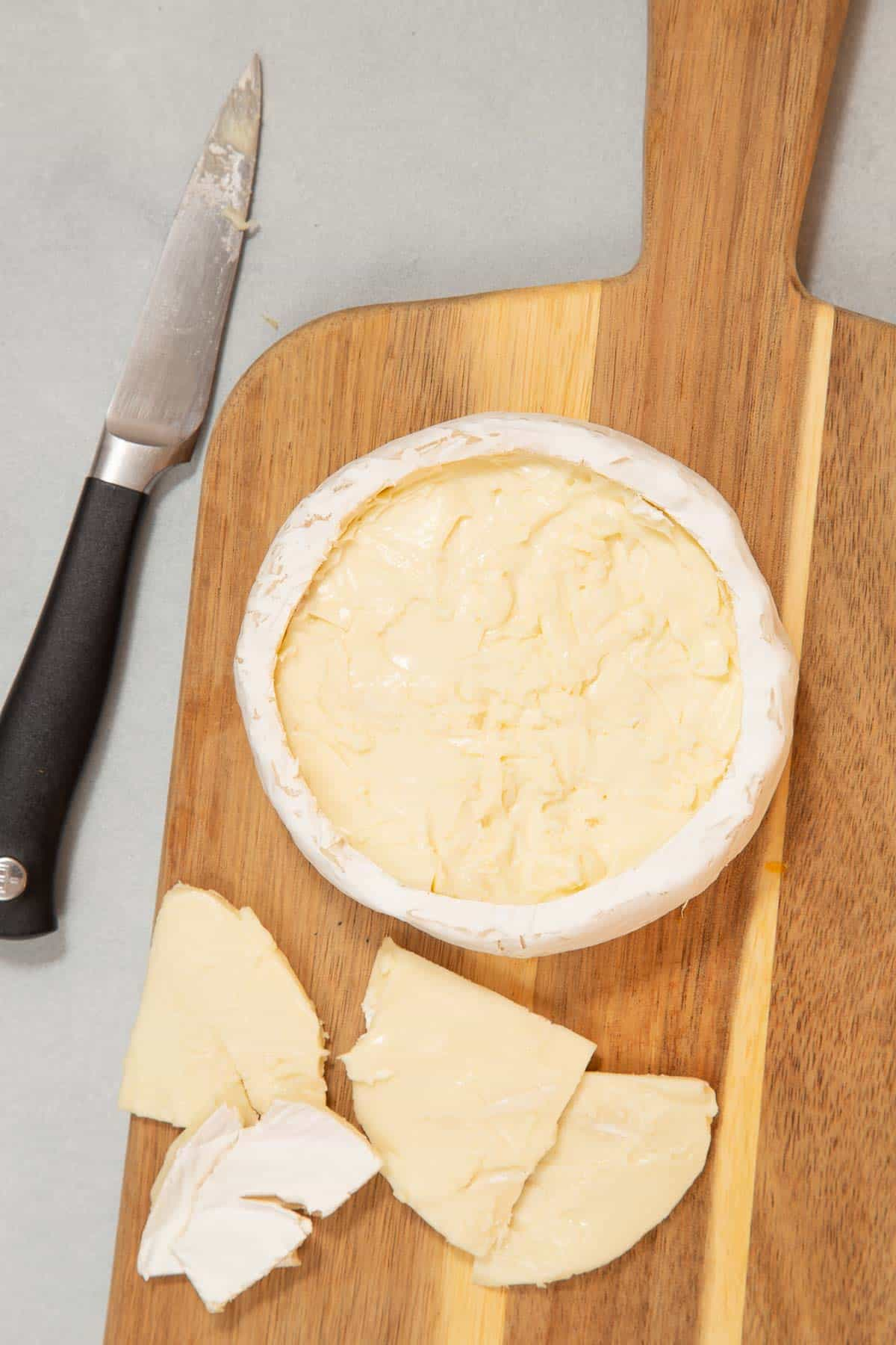 Wheel of brie on a wood board and a knife on the side