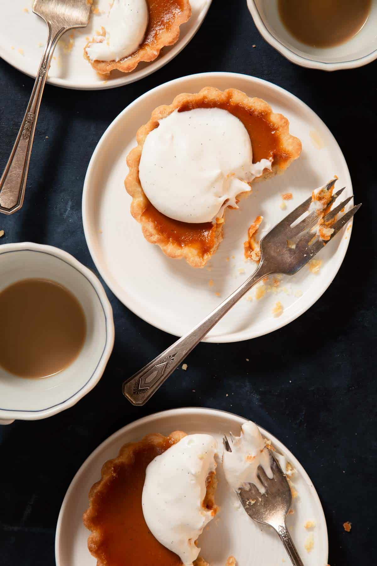 Half eaten mini pumpkin pie on a while plate with a fork