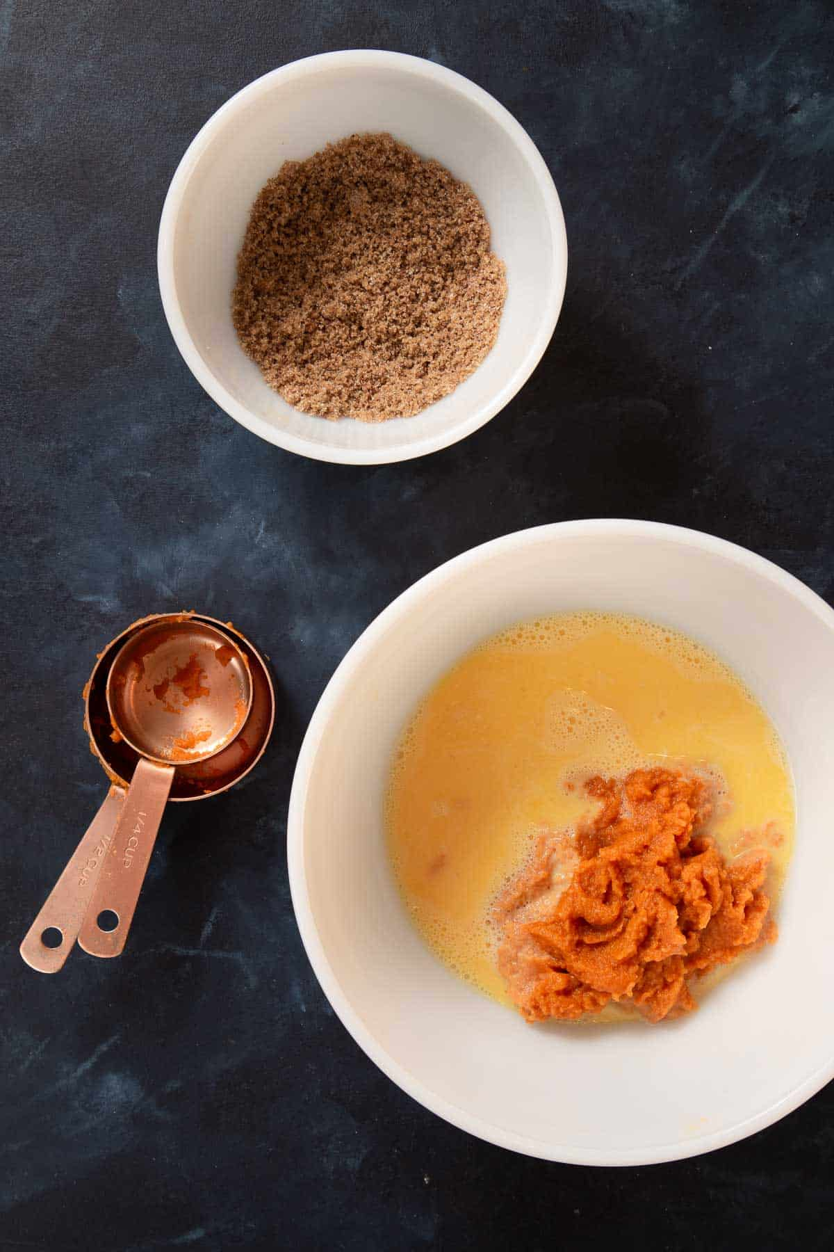 Small white bowl with brown sugar. A larger white bowl with egg yolks and pumpkin puree.