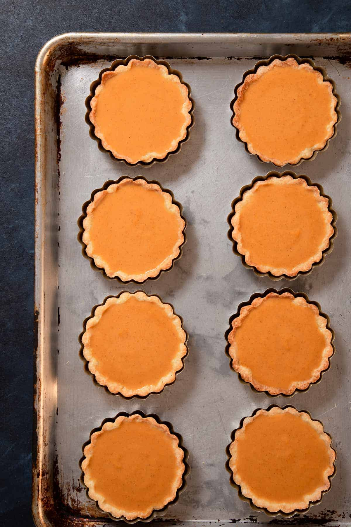 Individual tarts on a baking sheet filled with pumpkin pie filling