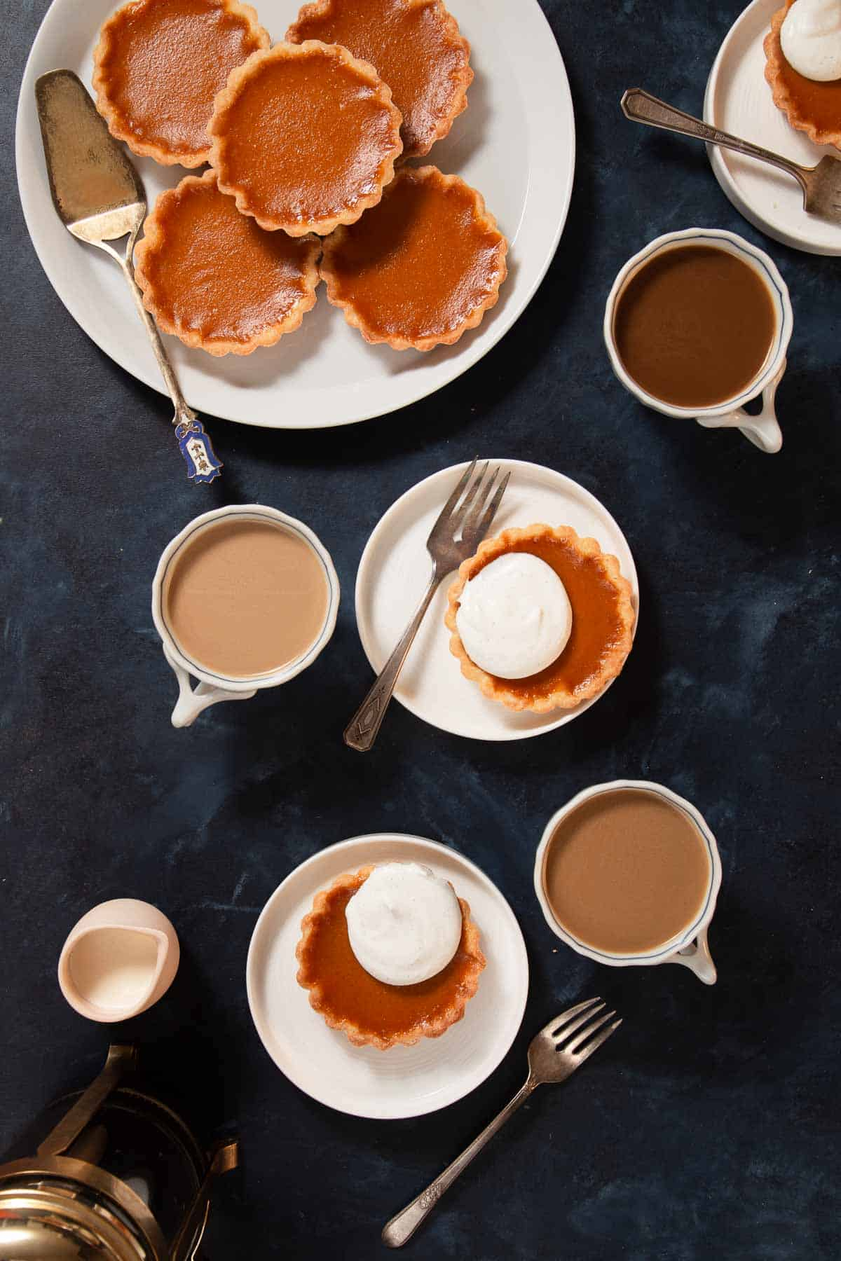 Serving mini pumpkin pies on white plates with coffee on the side