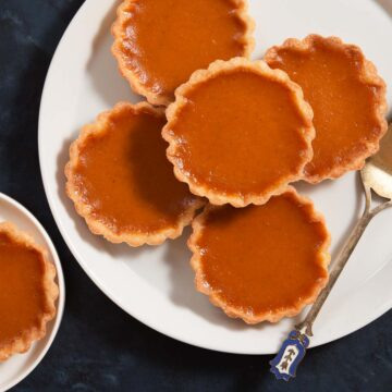 A pile of pumpkin pie tarts on a white plate