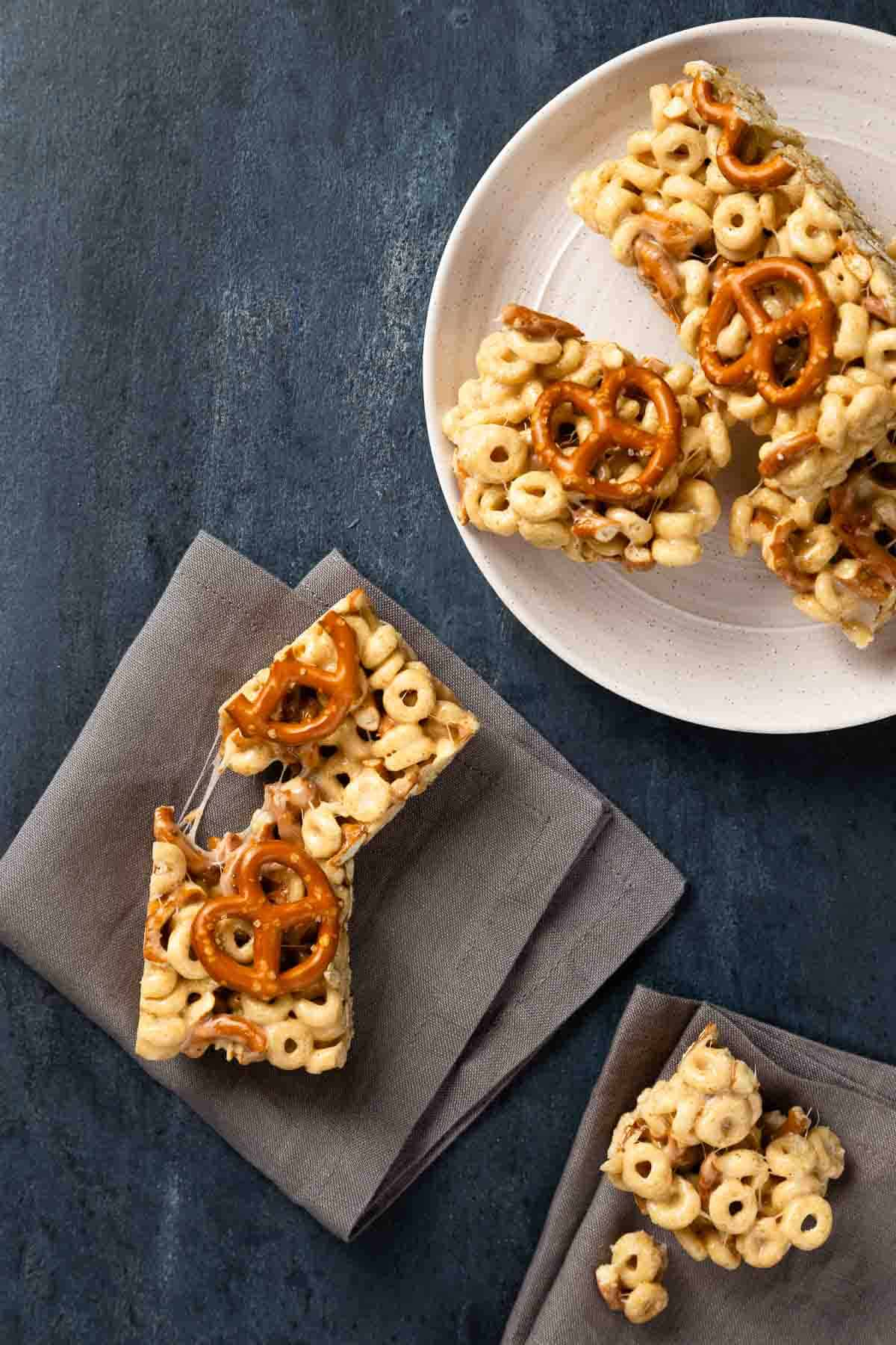 Cereal and pretzel bars on a white plate. One bar on the side on a black napkin.