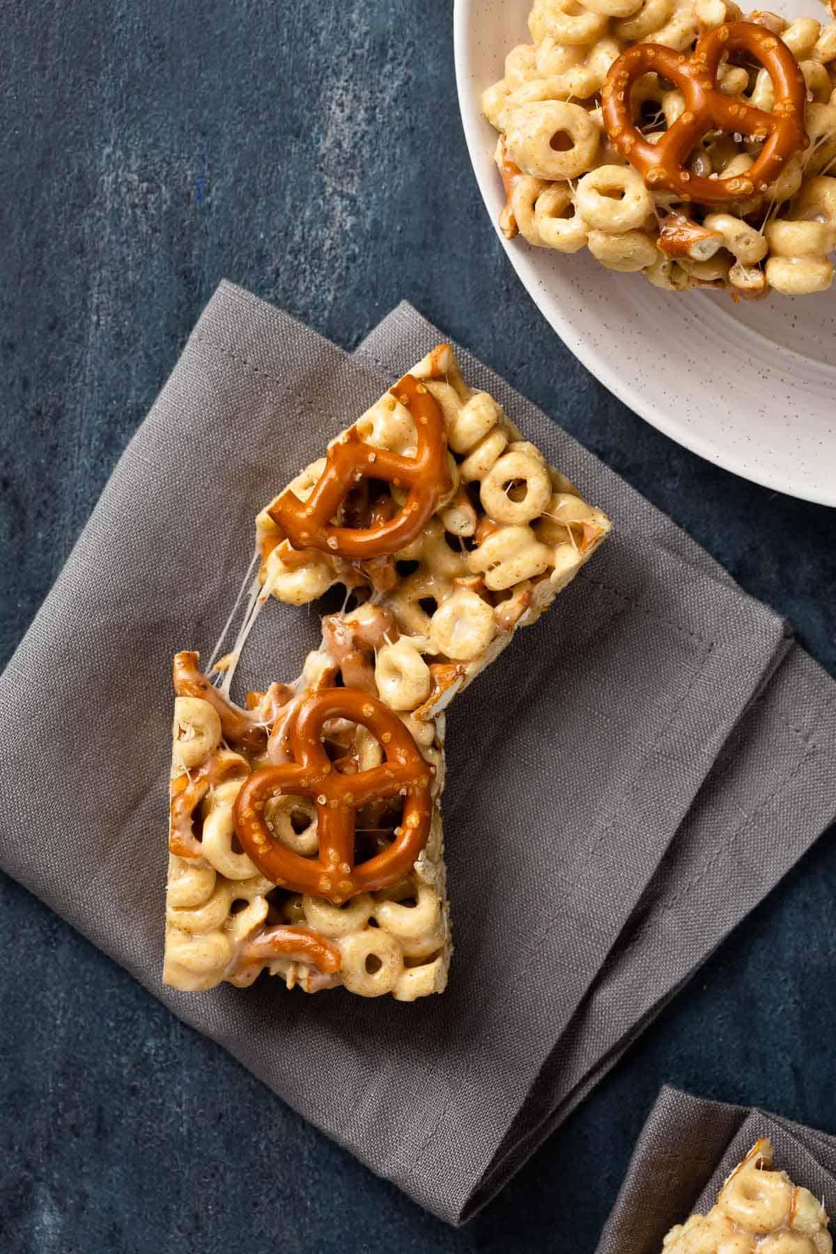 Cereal and pretzel bar torn in half on a black napkin