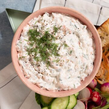 Close up of a pink bowl holding white dip with green herbs on top