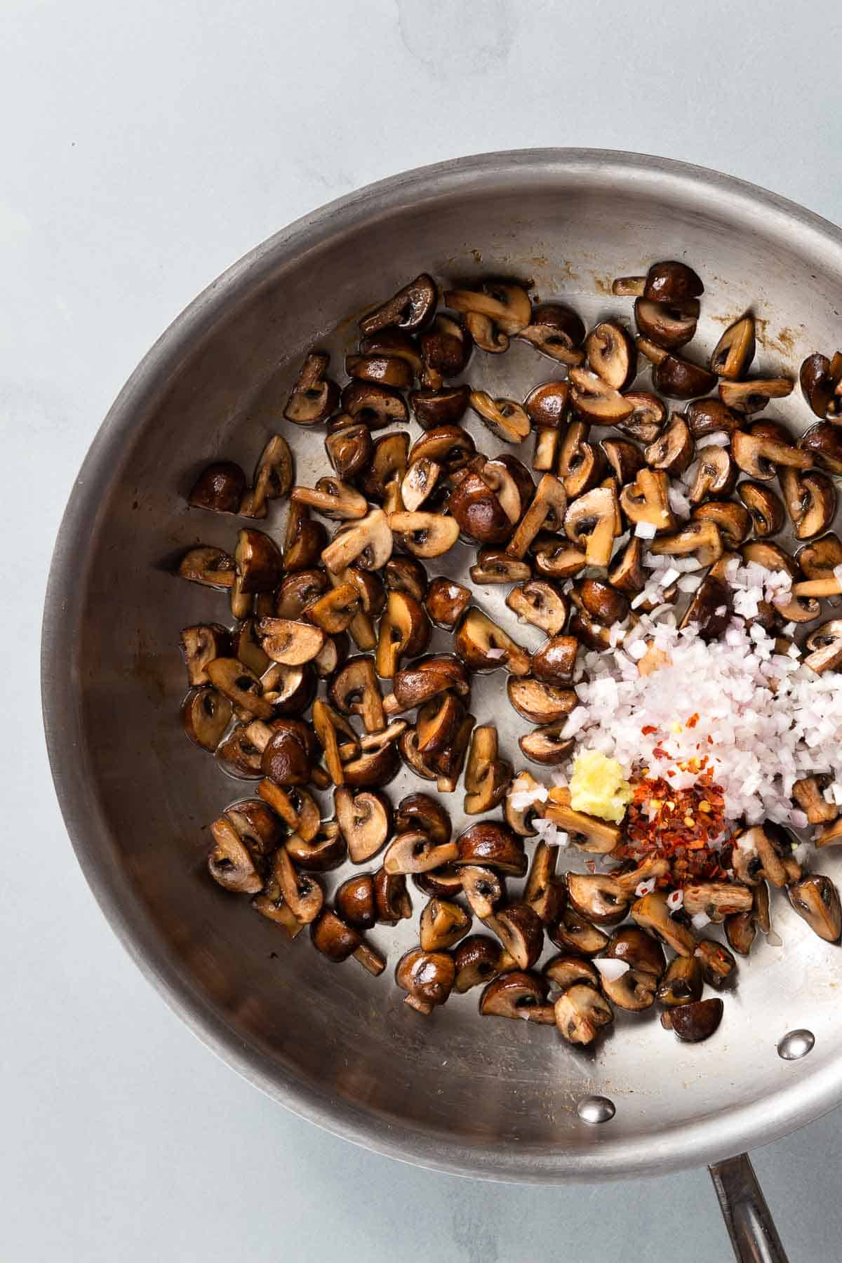 Cooking mushrooms with shallots and spices in a large metal pan