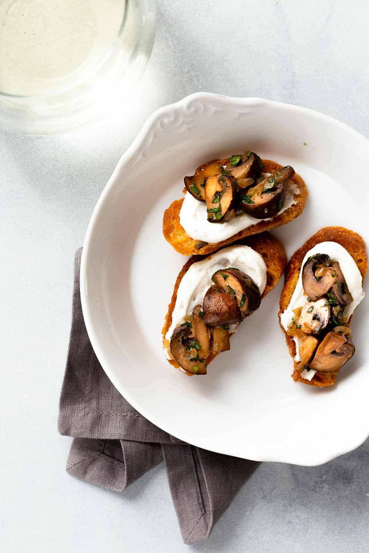 White serving dish with 3 crostini's with white sauce and mushrooms on top