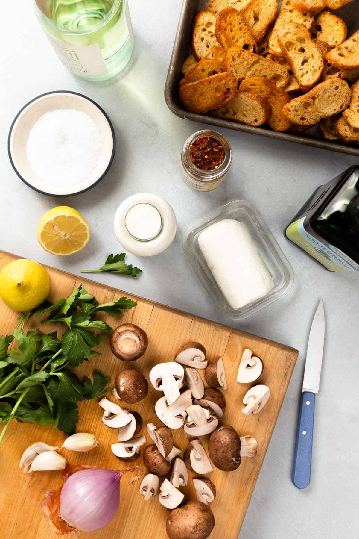 Chopping mushrooms and herbs on a large cutting board with crostini, goat cheese, salt, and lemon on the side