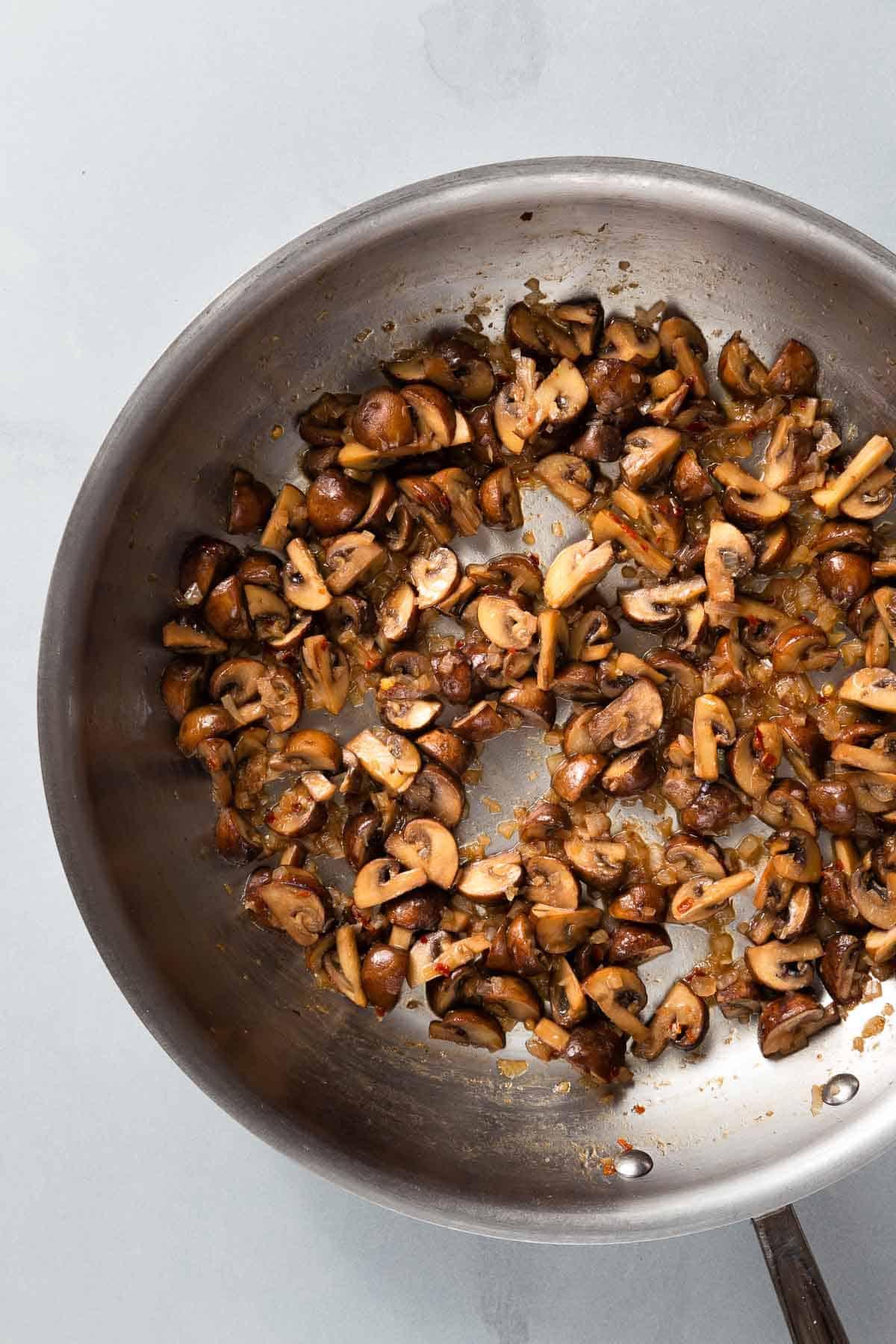 Cooking mushrooms in a large metal pan
