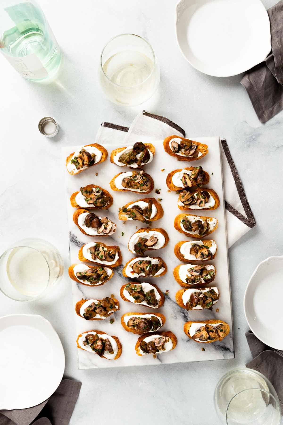 Large white marble slab holding crostini's with mushrooms on top