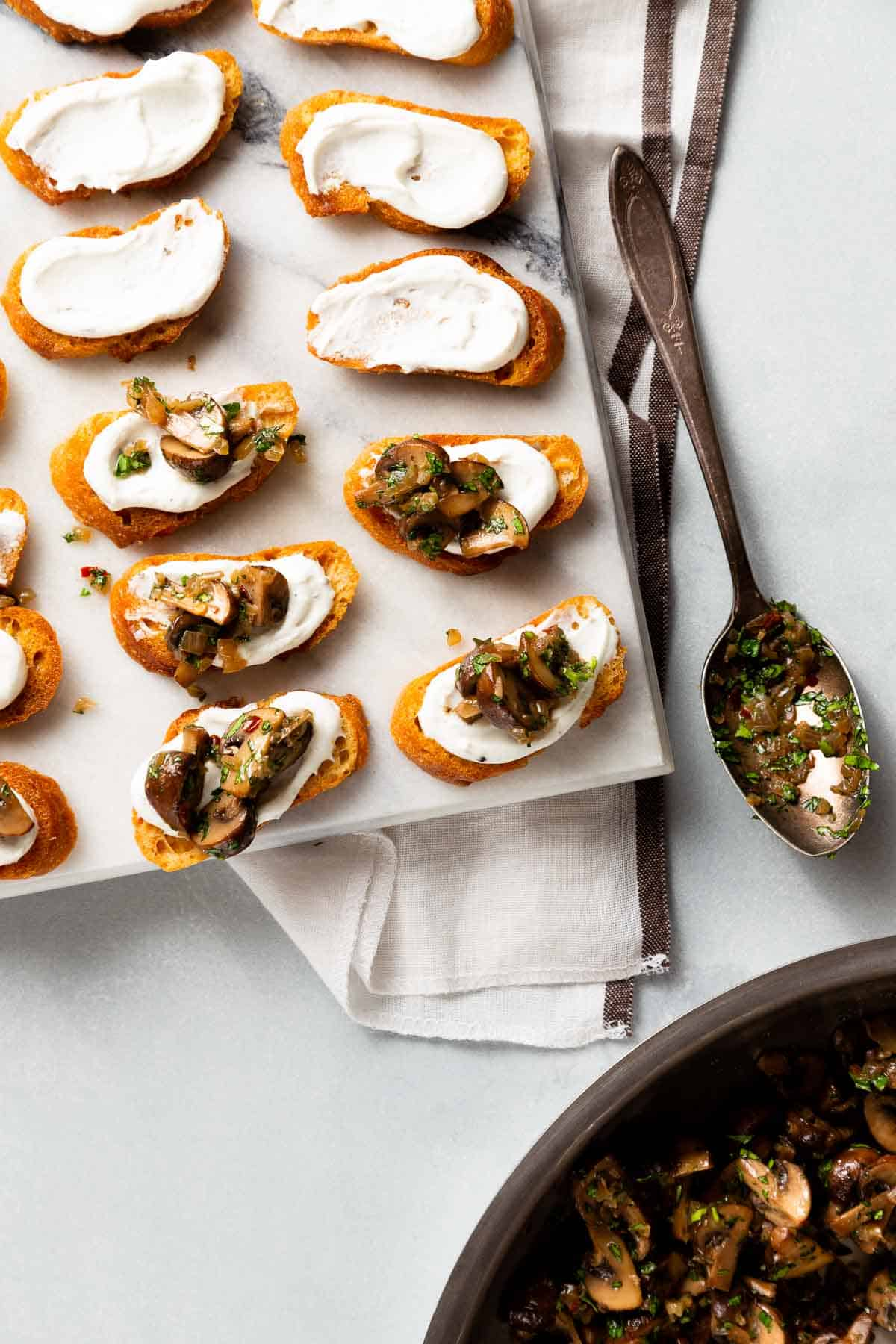 Using a spoon to scoop mushrooms on top of goat cheese spread on a crostini