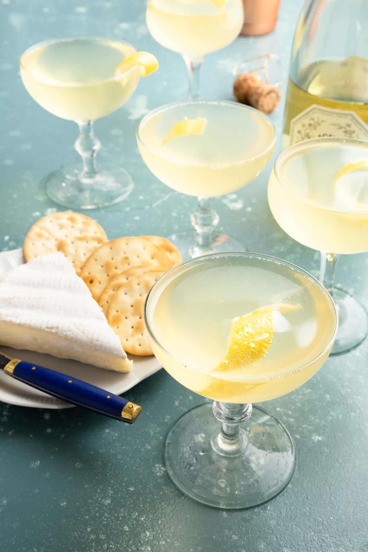 Multiple glasses of yellow cocktails with cheese and crackers on the side