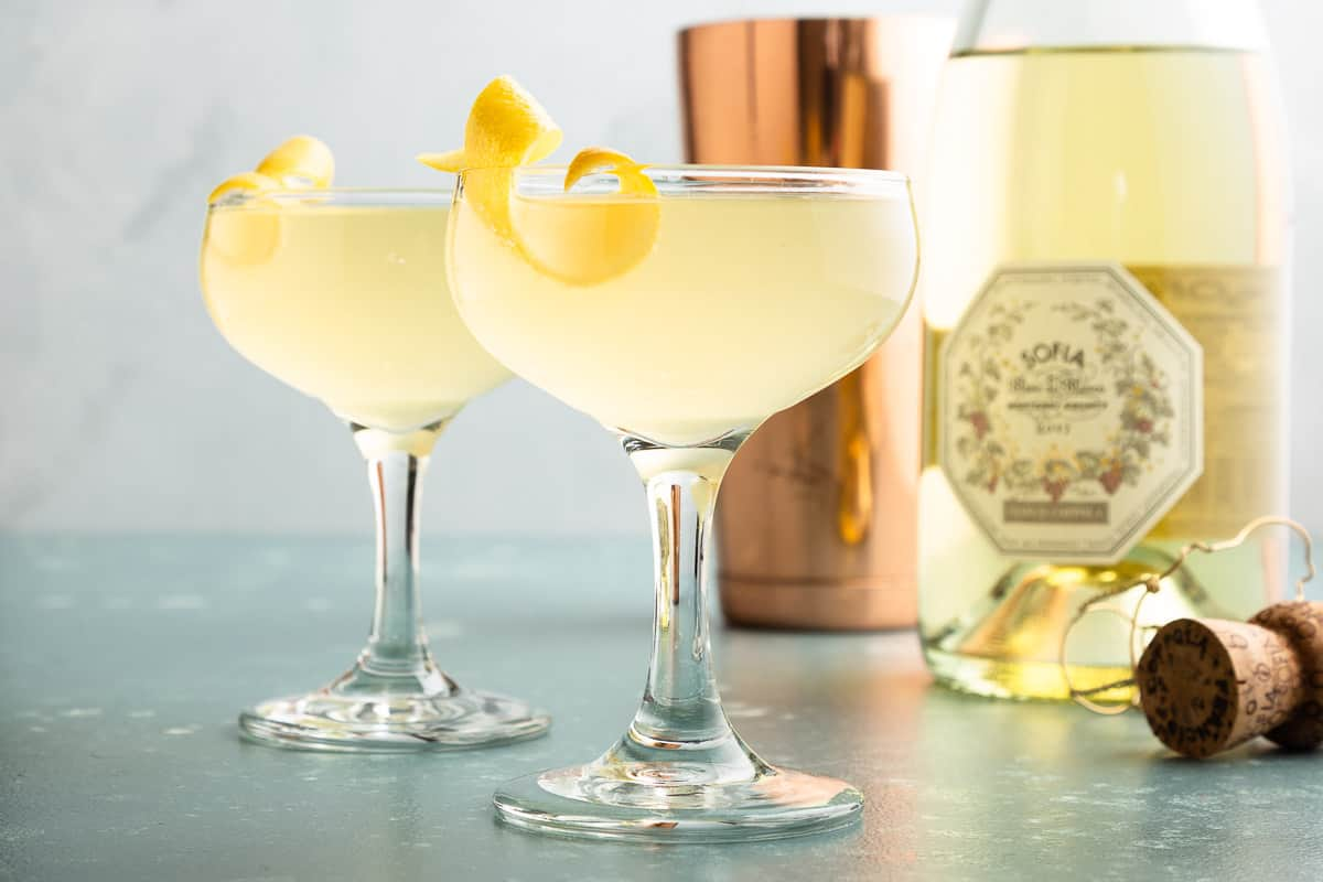 2 glasses of pale yellow cocktails with a lemon twist