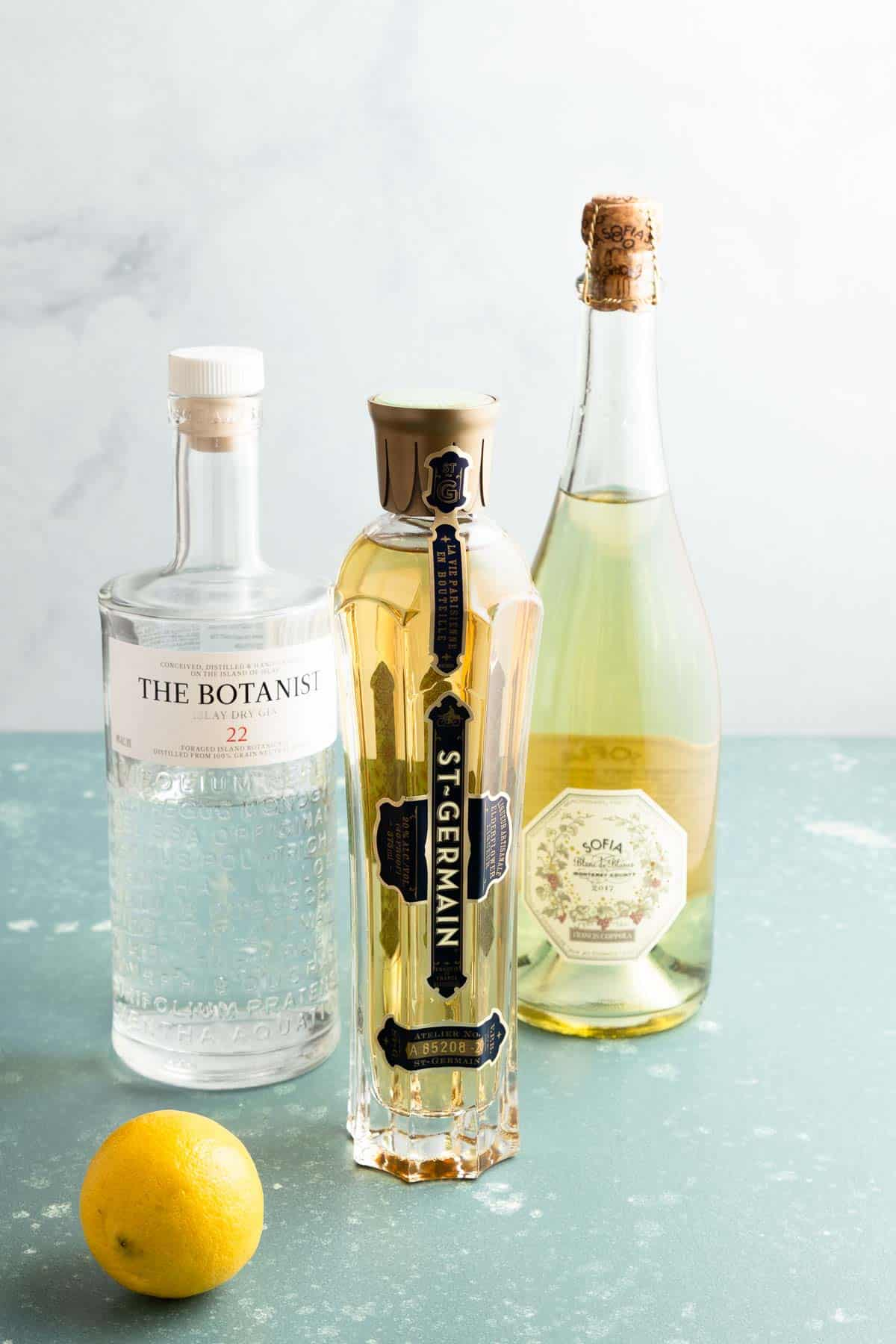 A bottle of gin, sparkling wine, and elderflower liqueur and a lemon on the side