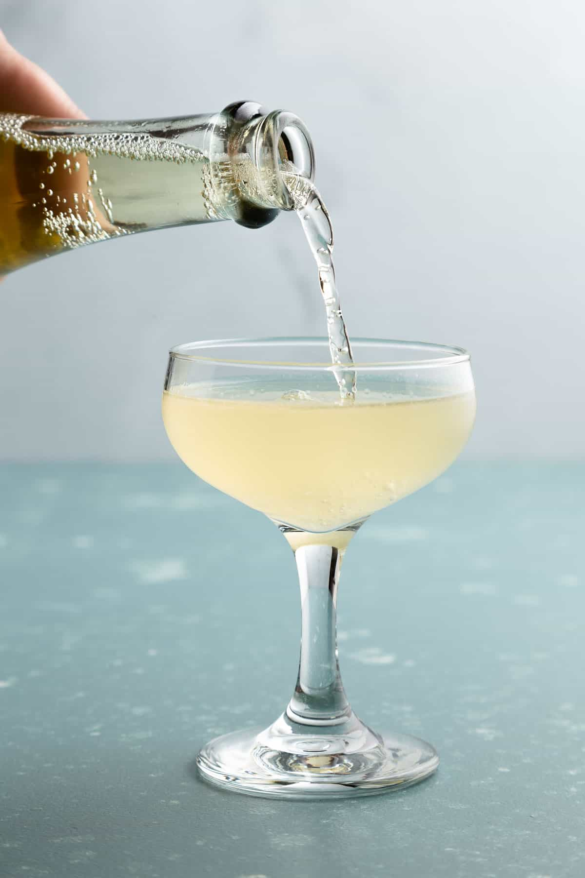 Pouring sparkling liquid into a cocktail glass