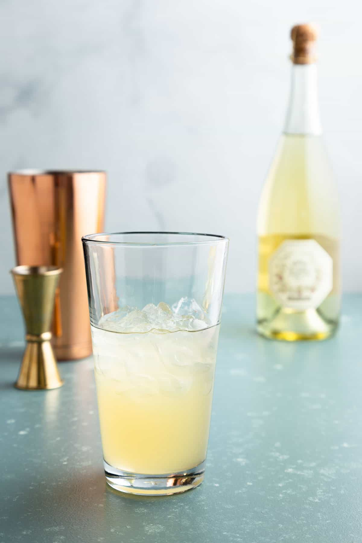 Tall glass with ice and yellow liquid. Bottles and cocktail shaker in the background.