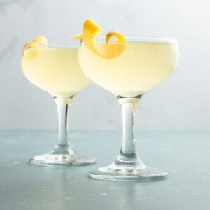 2 glasses of yellow French 77 cocktails with lemon twists