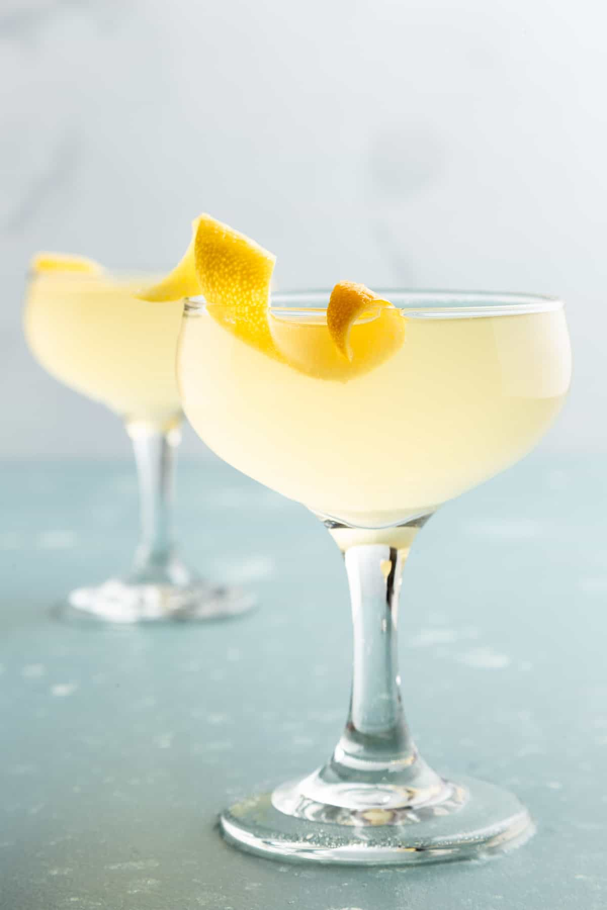 Closeup of a yellow cocktail with a lemon twist