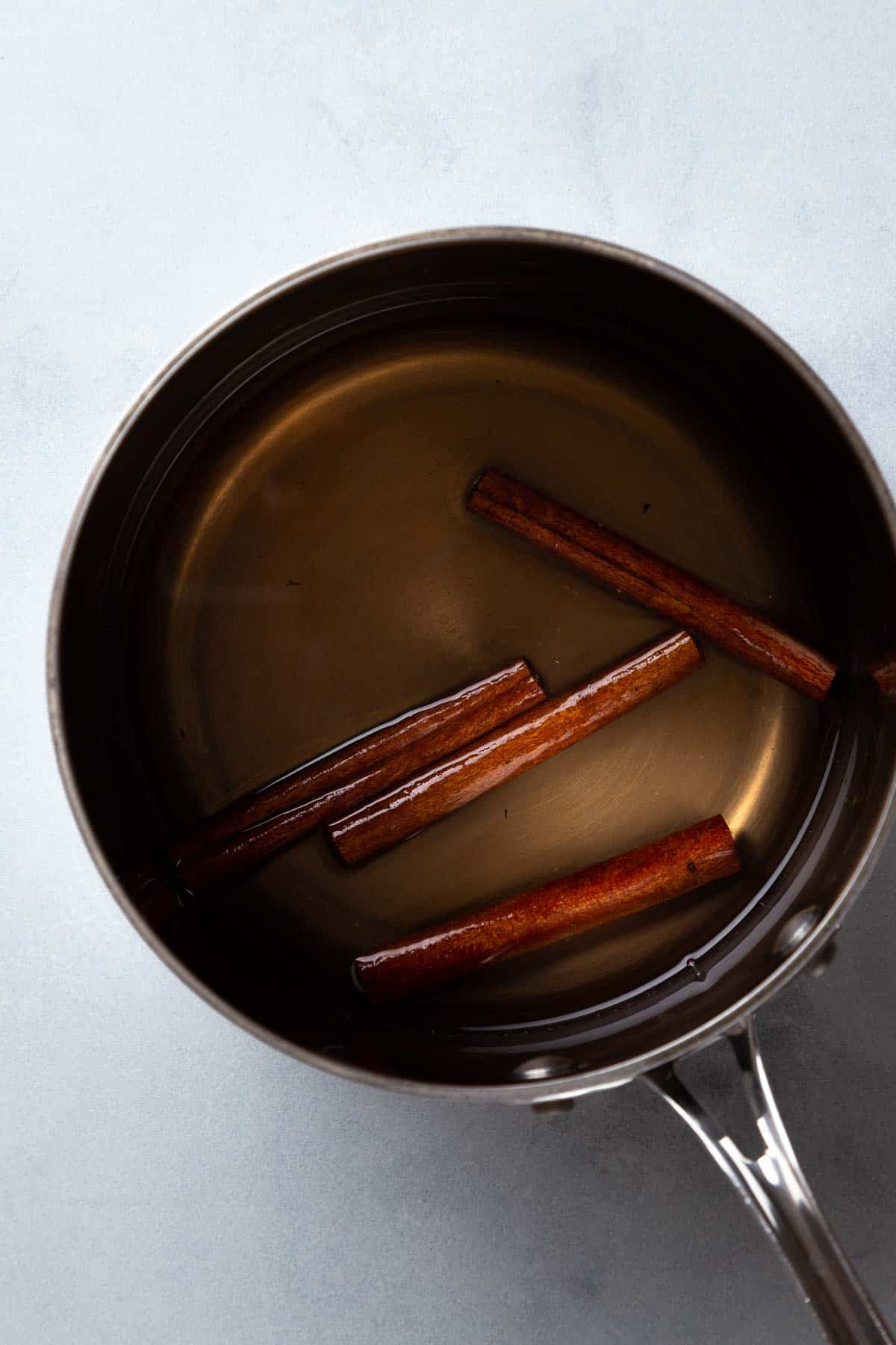 Cinnamon sticks and simple syrup in a saucepan