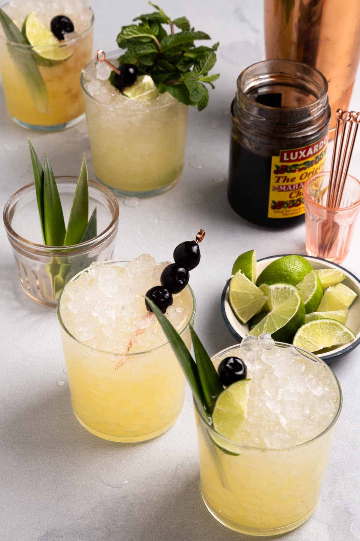 Glasses of yellow mocktails next to limes and garnishes
