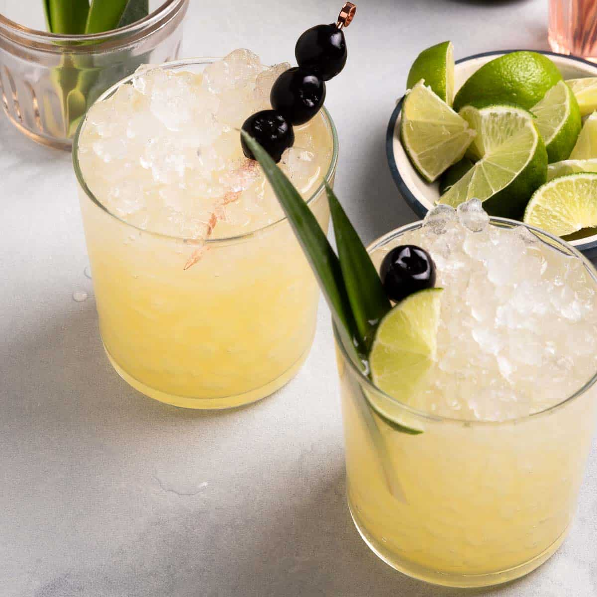 Two glasses of a yellow drink with lots of ice next to a small bowl of limes