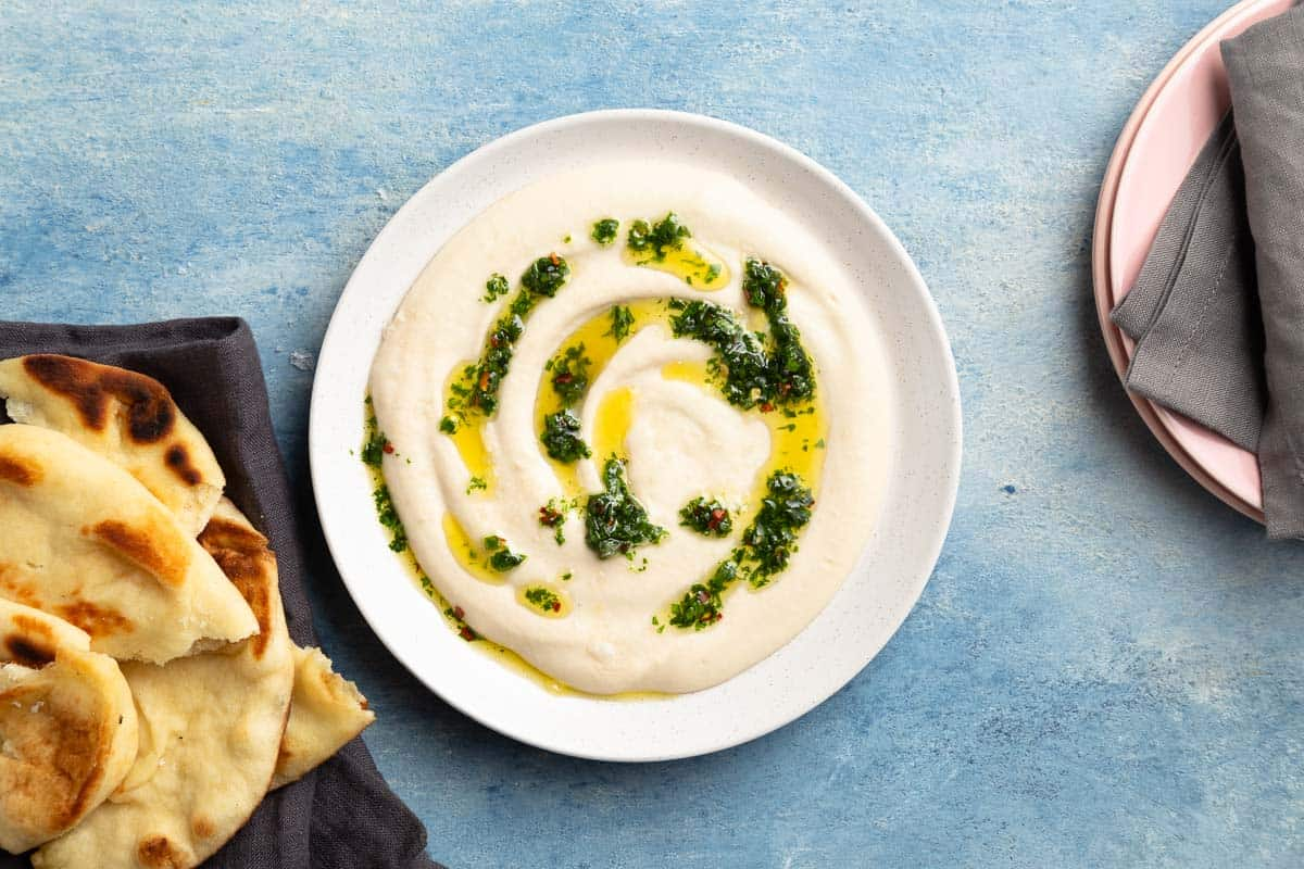 White dip with herbs and oil on top next to pita bread