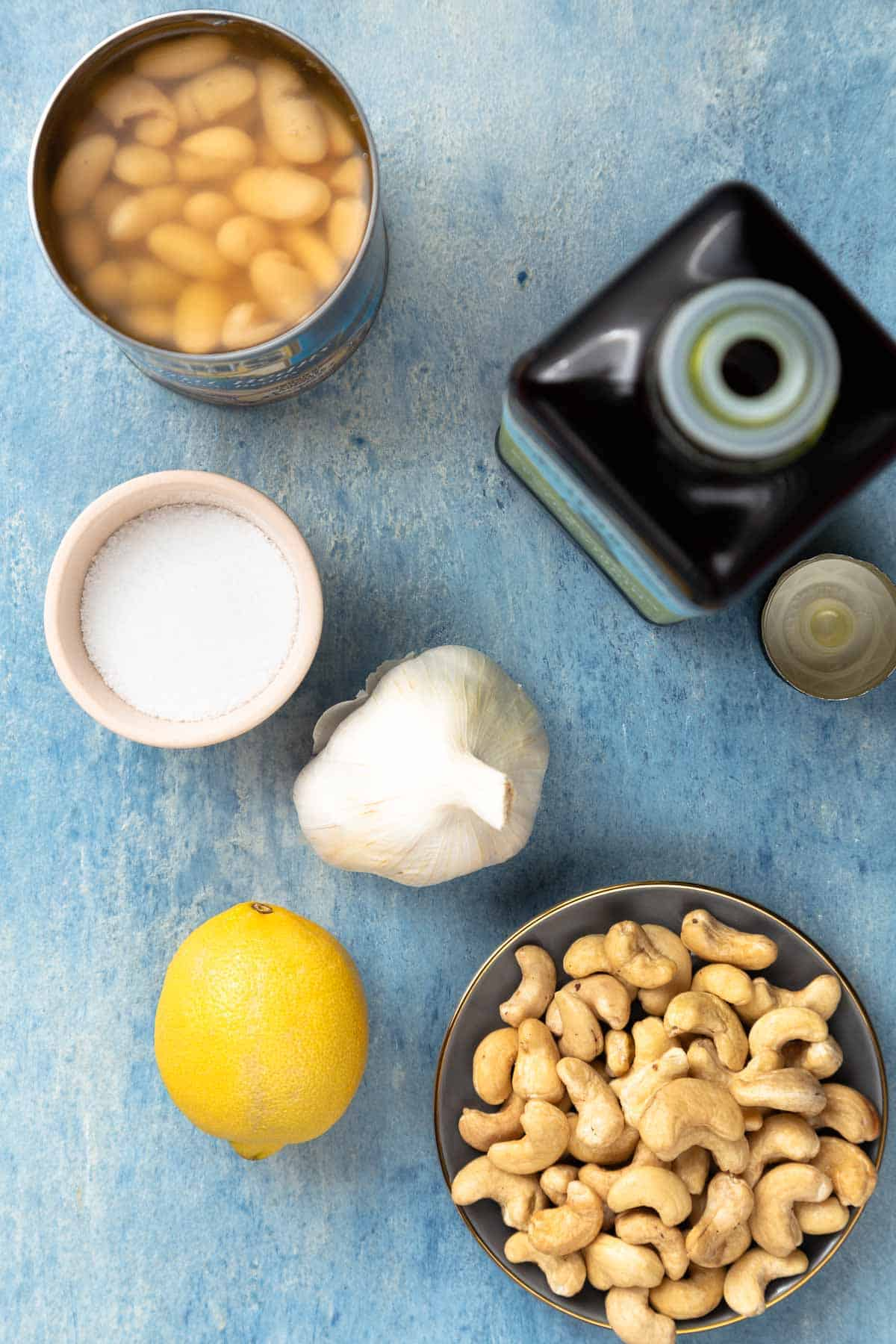 White beans in a can next to salt, oil, a bulb of garlic, lemon, and a bowl of cashews