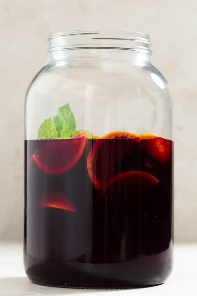 Large glass jug filled with red wine, oranges, and mint leaves