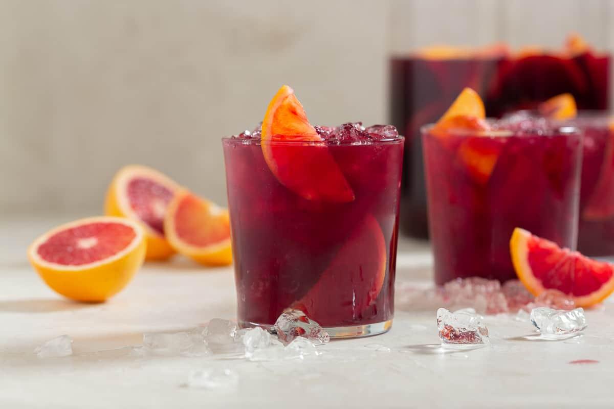 Dark red cocktails with orange garnish and blood oranges in the background