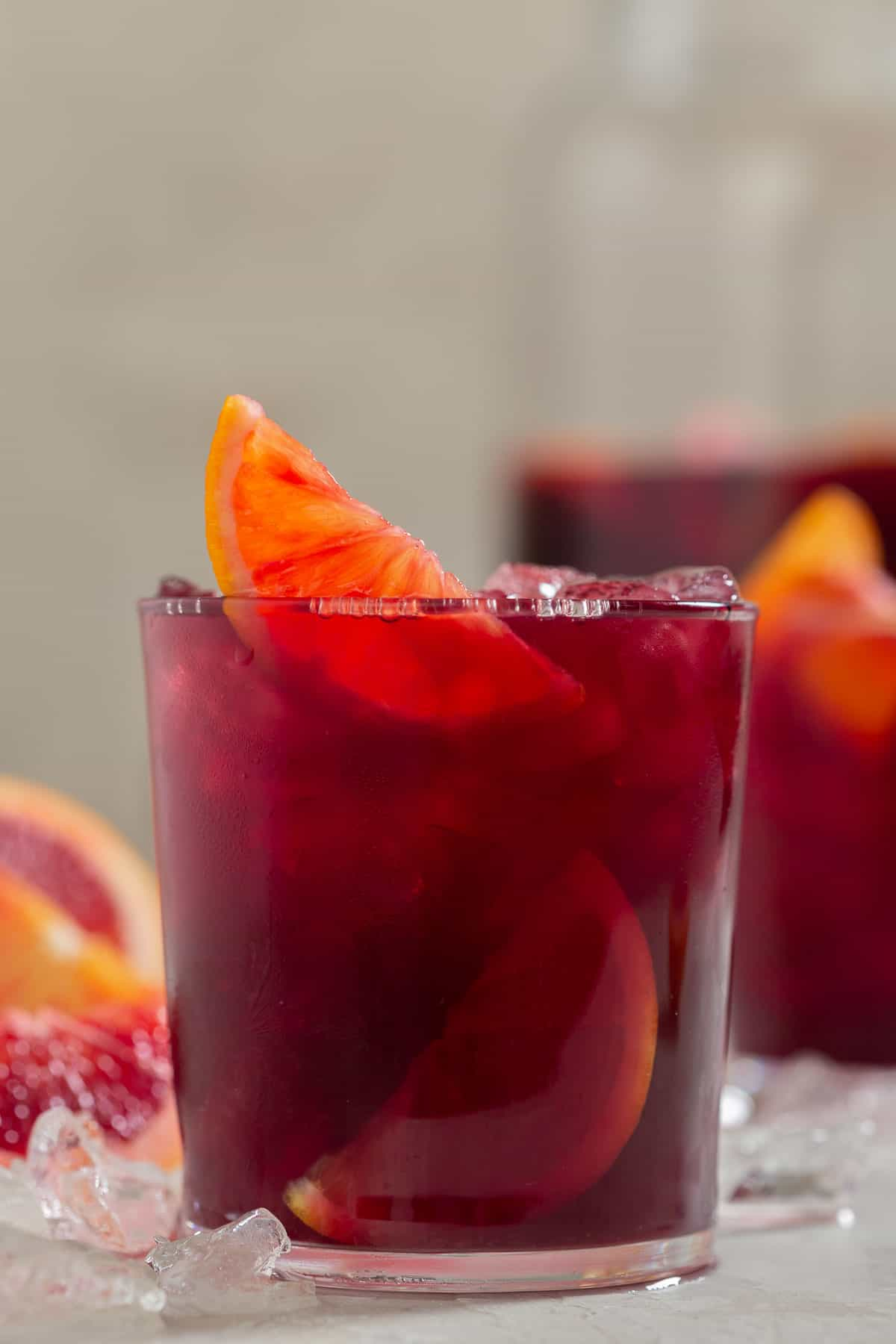 Close up of a dark red cocktail garnished with orange slices
