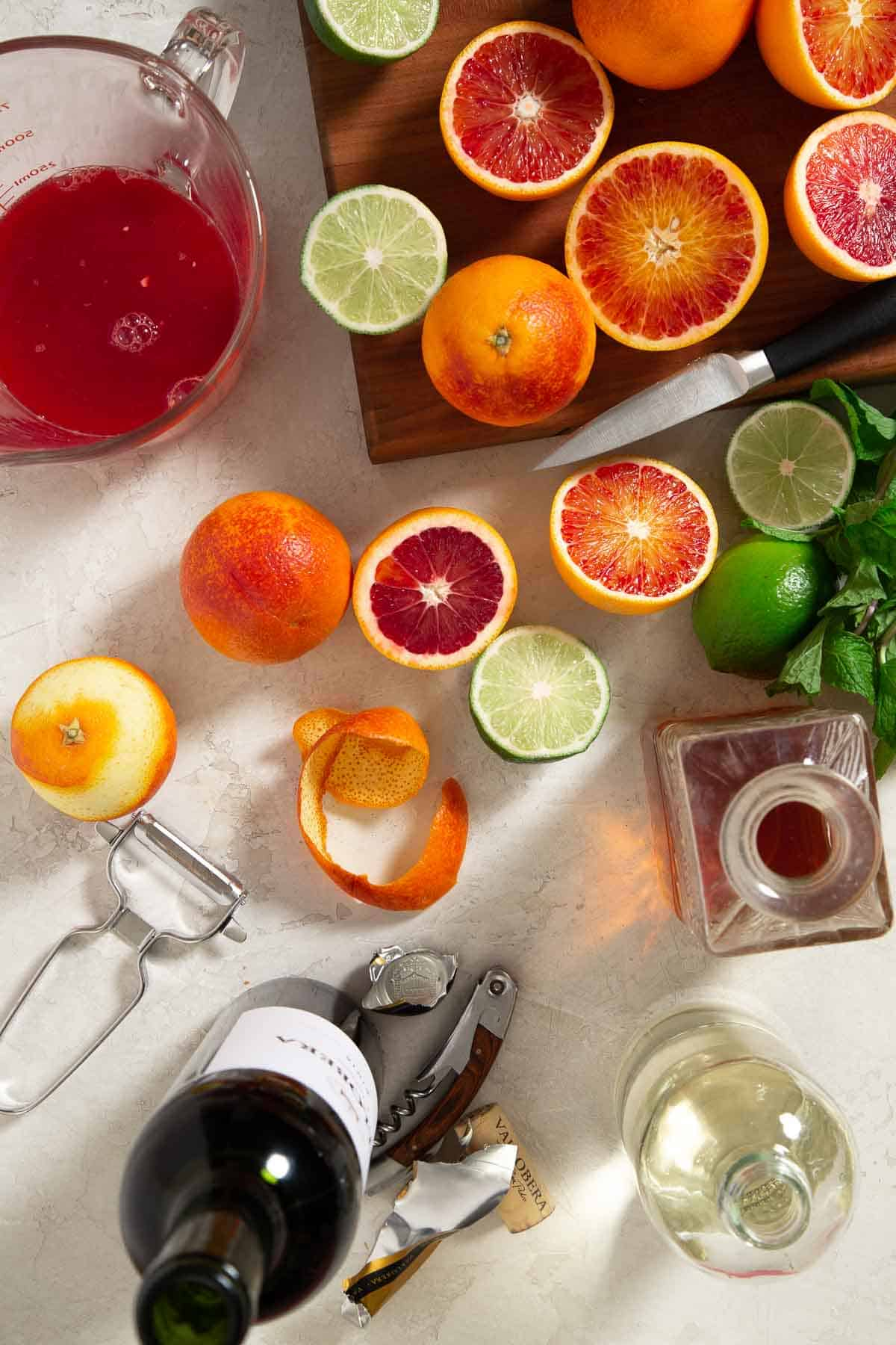 Overhead view of sliced oranges and limes next to bottles of liquor
