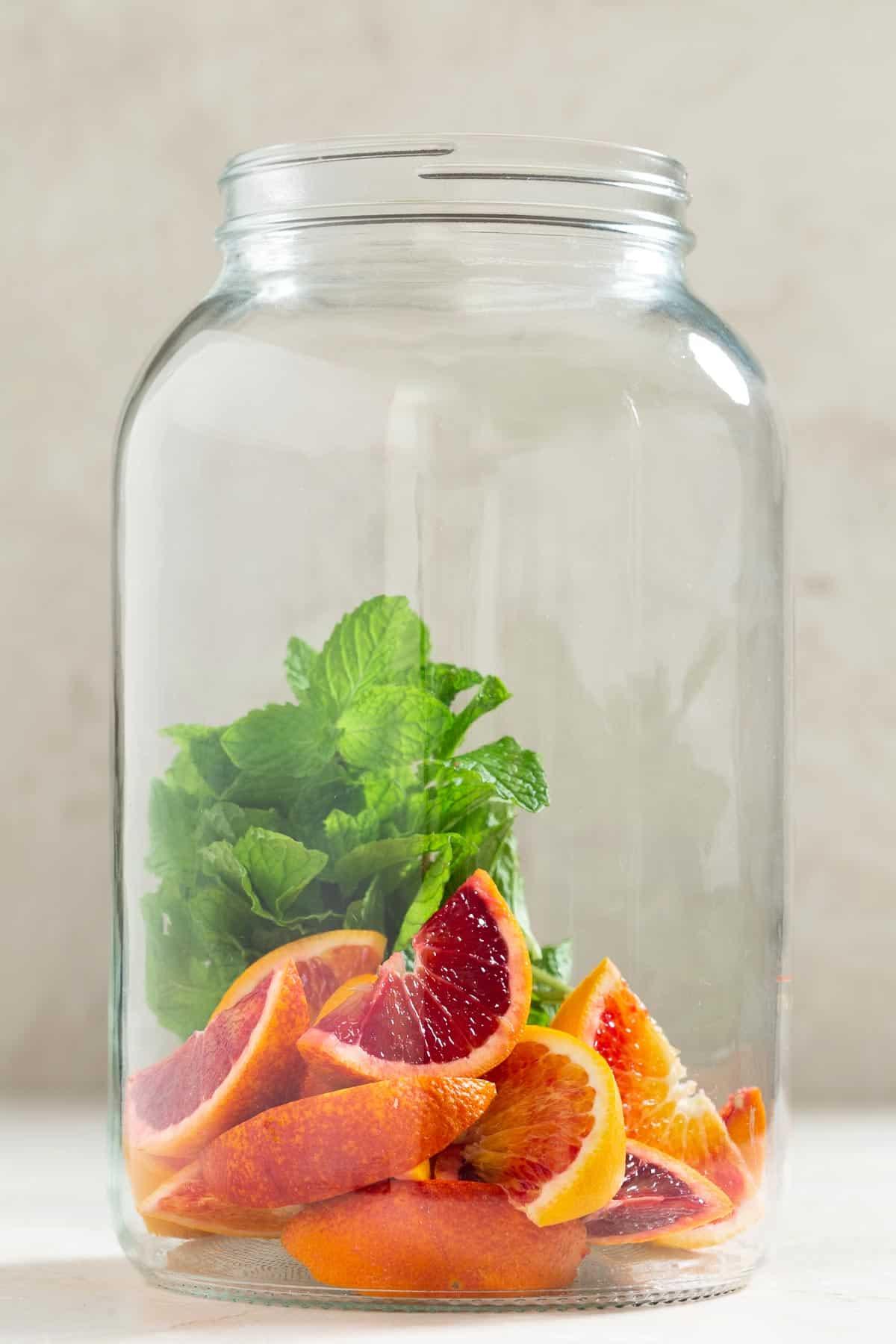 Large glass jug half full of orange slices and mint leaves
