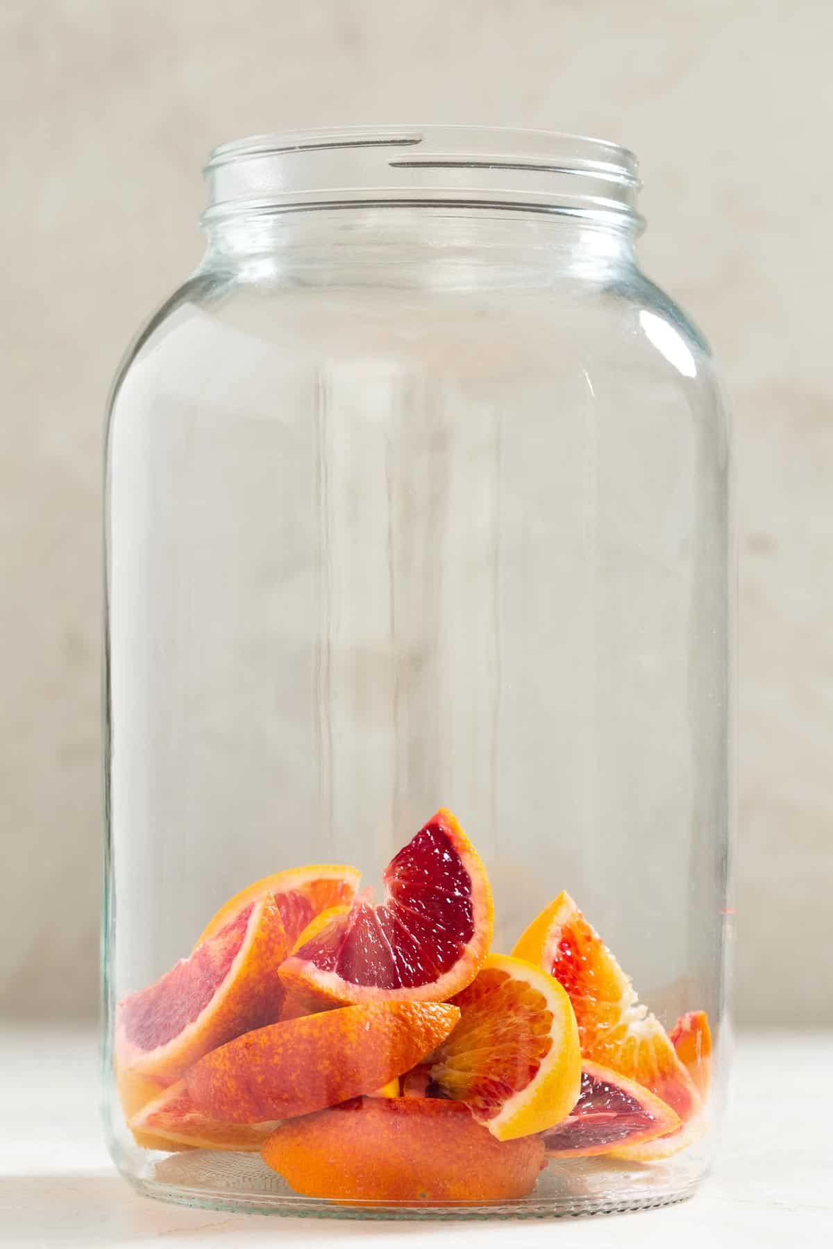 Large glass jug with slices of blood oranges on the bottom