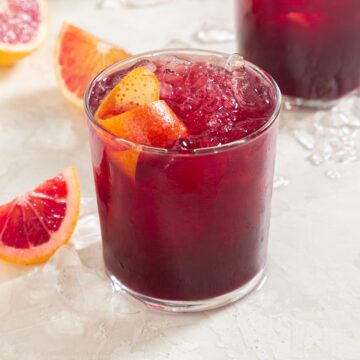Close up of a dark red cocktail with an orange twist