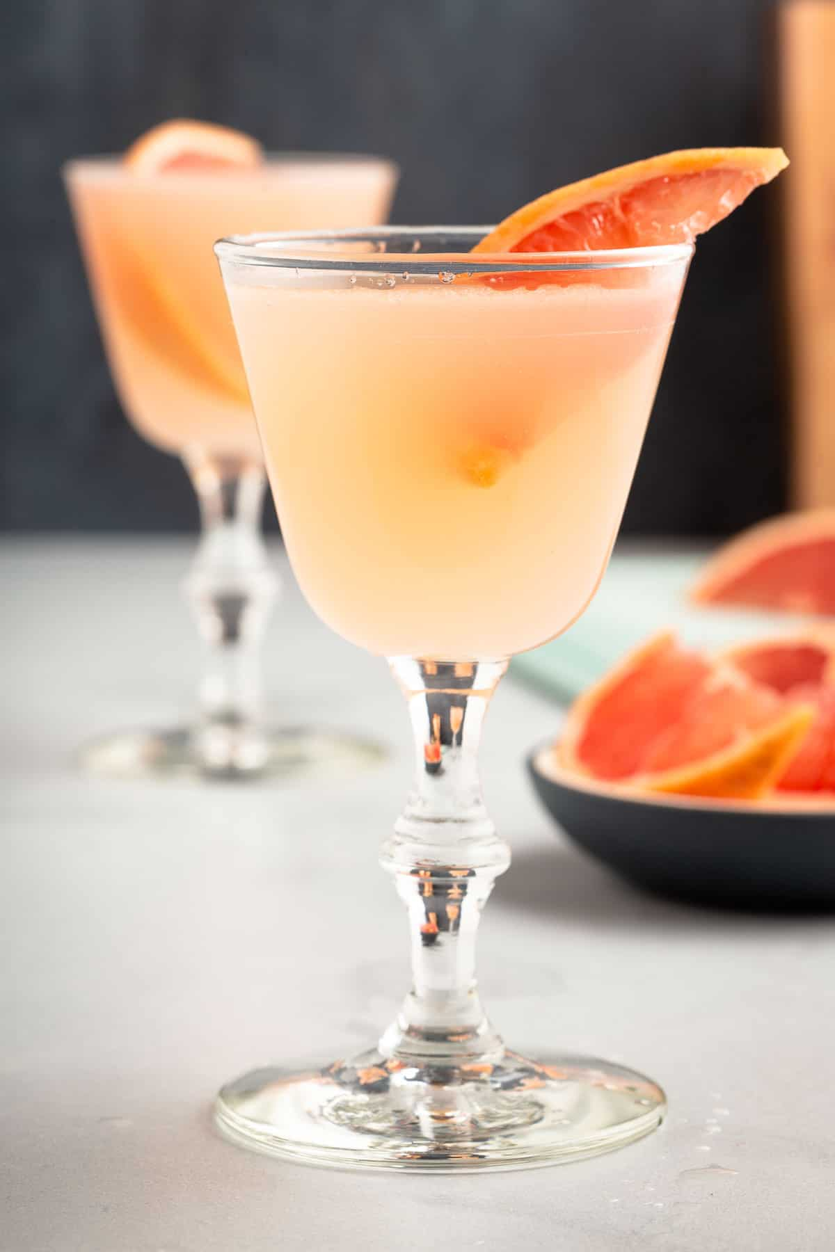 pink cocktail in a stemmed glass garnished with a slice of grapefruit