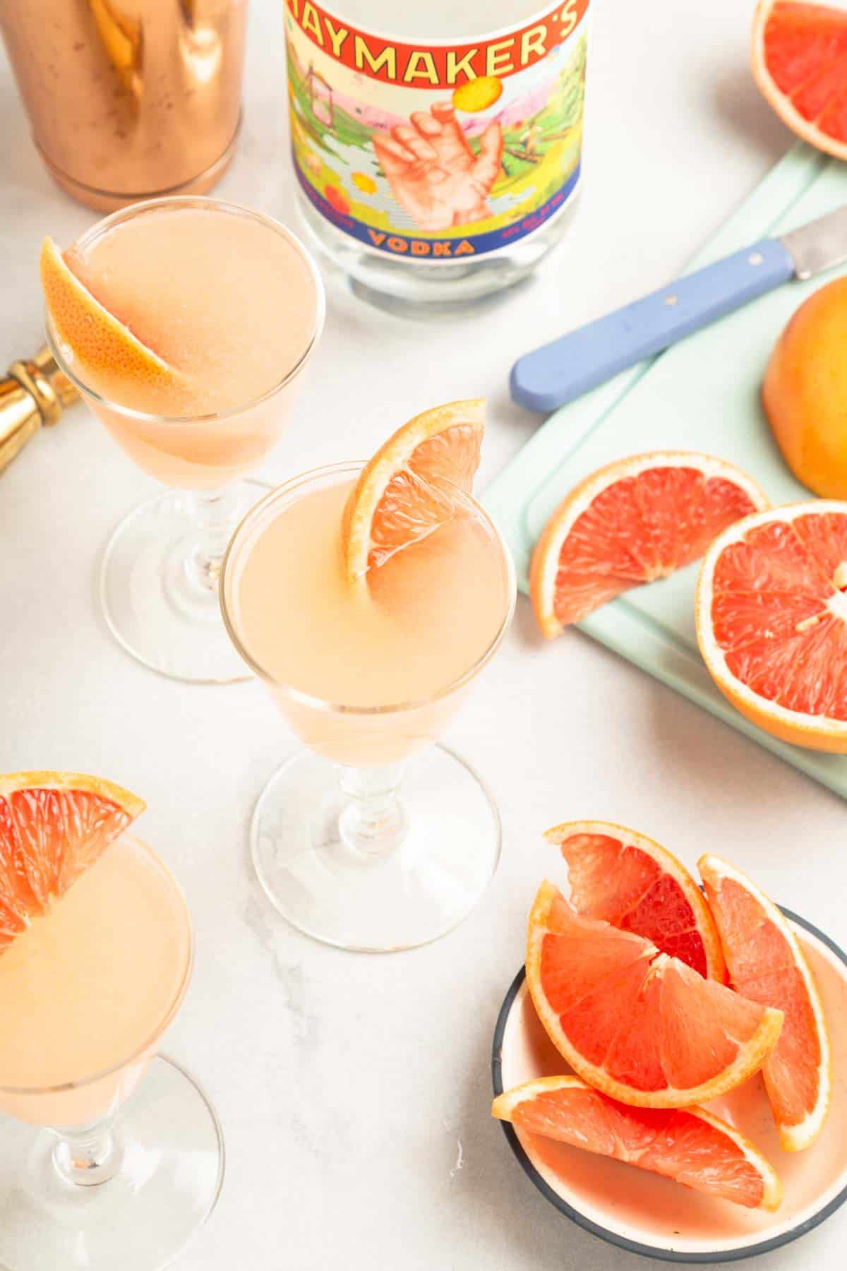 overhead view of multiple pink cocktails next to slices of grapefruit