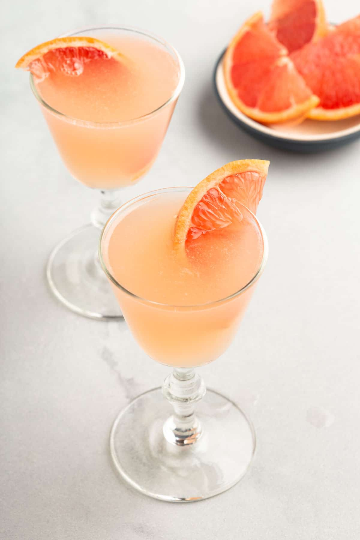 2 grapefruit cocktails garnished with sliced of grapefruit