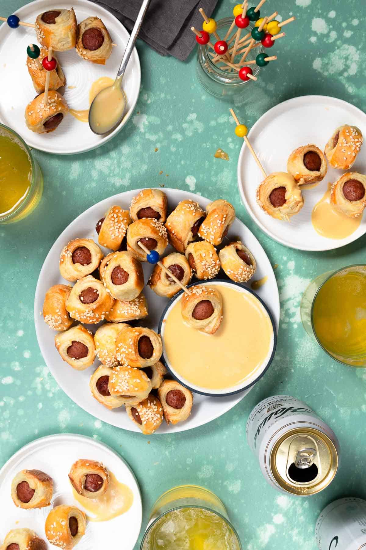 four white plates holding pigs in a blanket and honey mustard dip next to beer