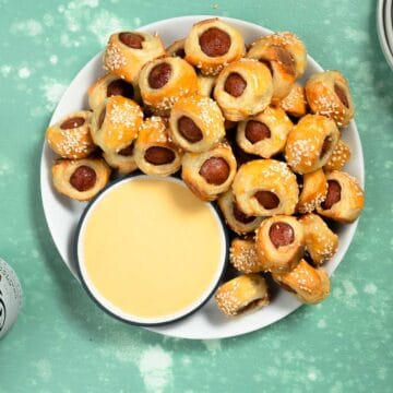 white plate full of pigs in a blanket next to a bowl of honey mustard sauce