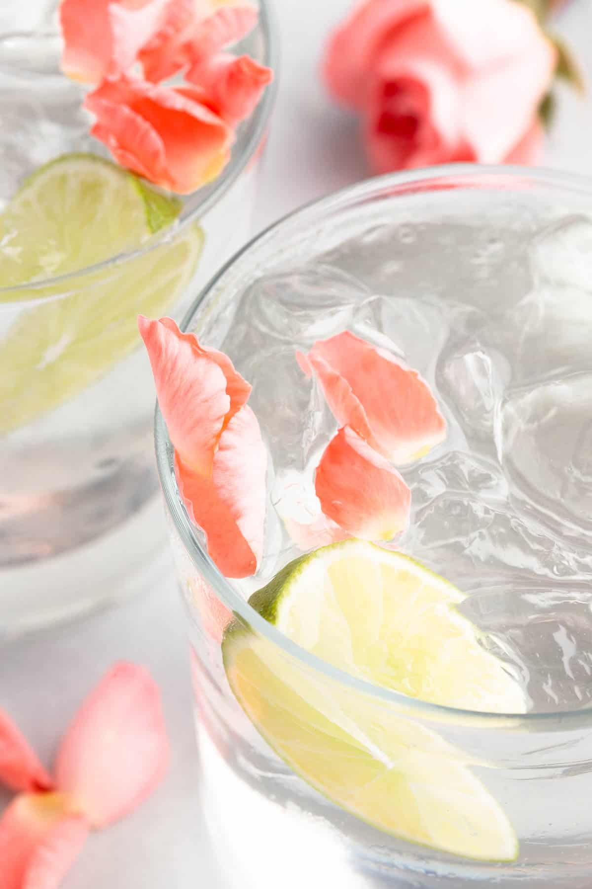 close up of 2 gin and tonics in a rocks glasses with flower petals and lime