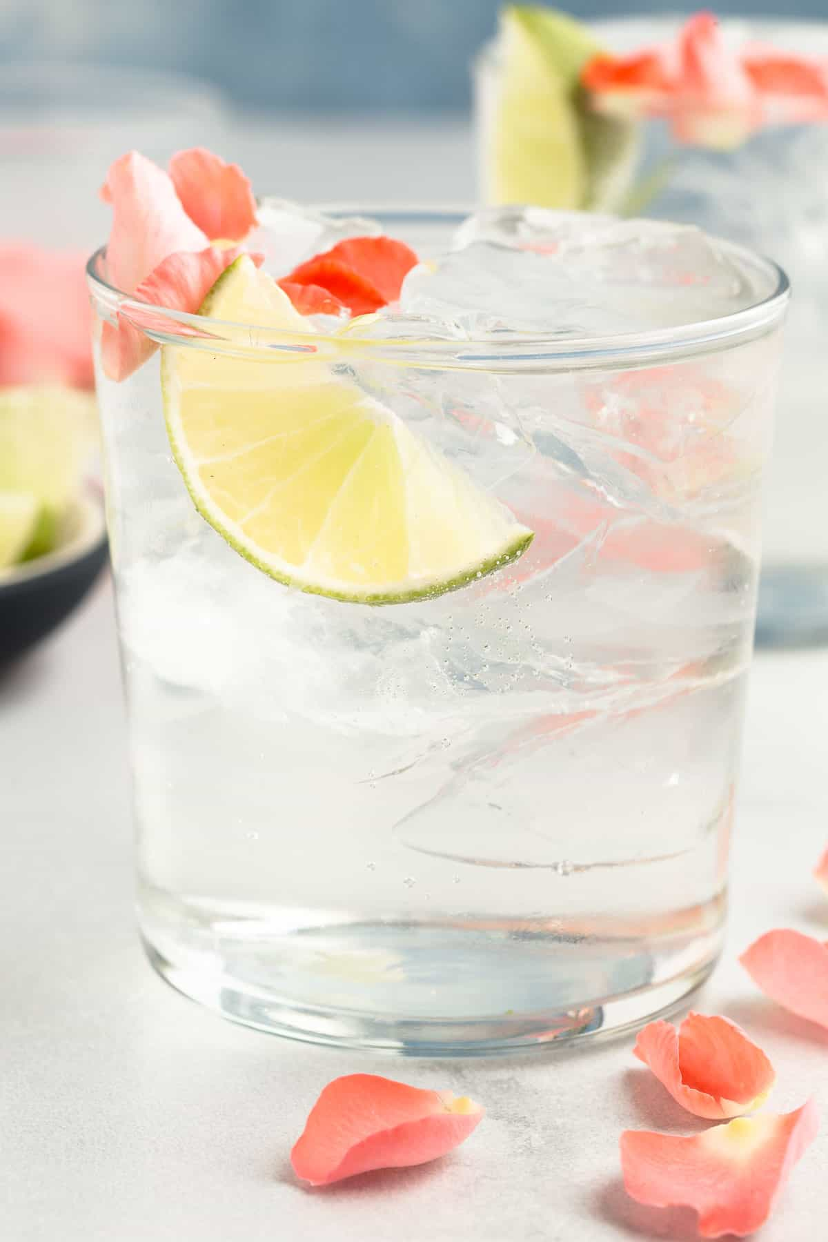 close up of a gin and tonic in a rocks glass with rose petals and lime