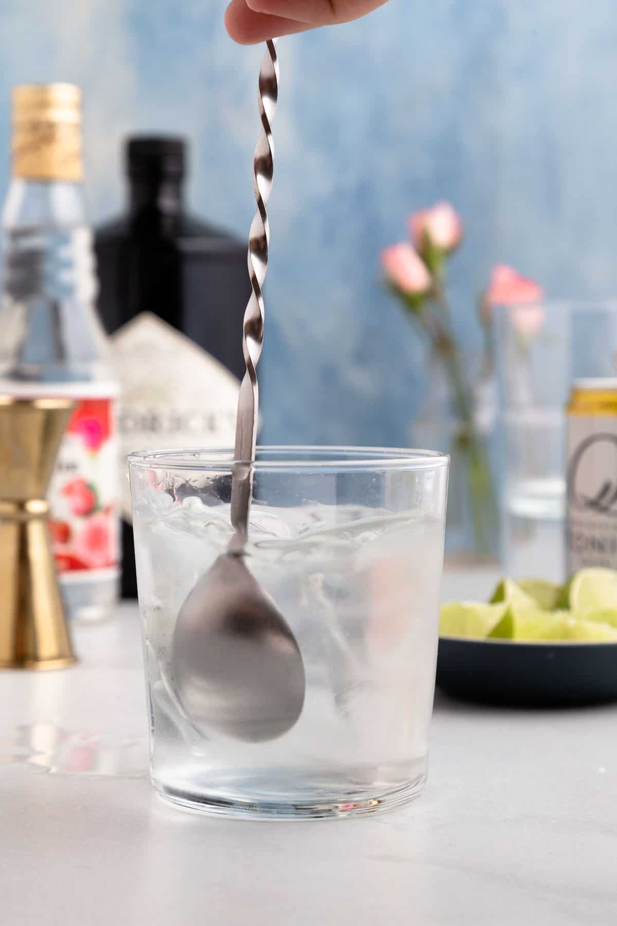 cocktail spoon stirring a clear cocktail in a small glass