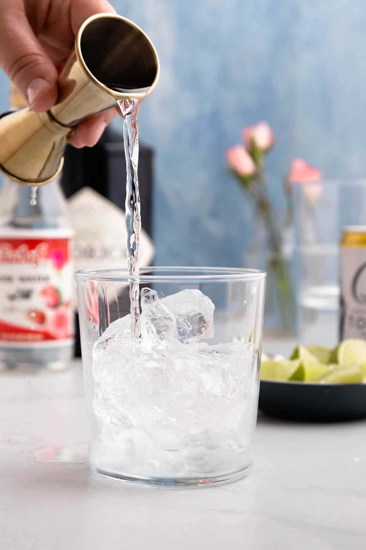 pouring clear liquor into a glass with ice