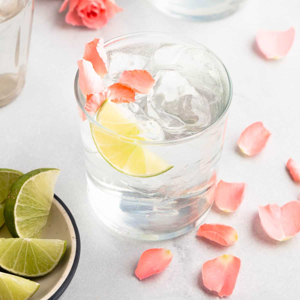 gin and tonic in a rocks glass with flower petals and lime