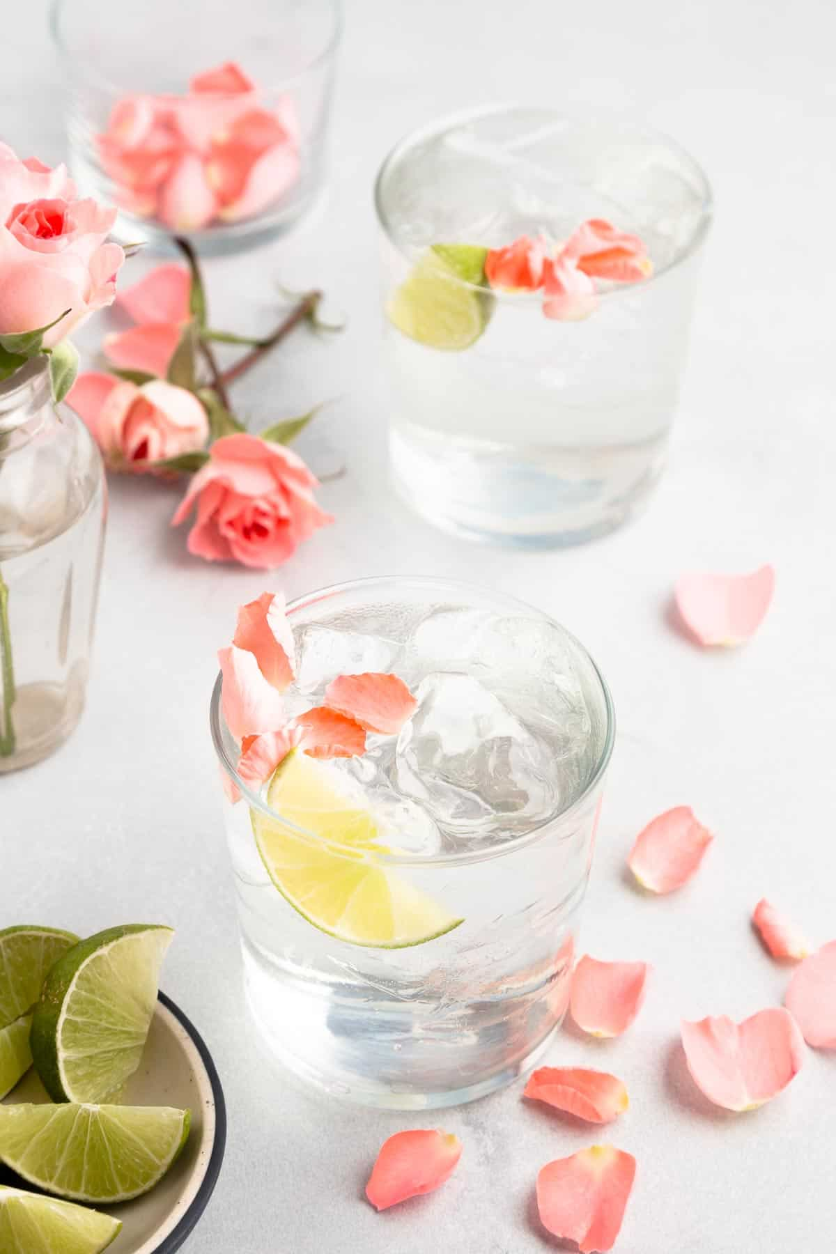 2 gin and tonics in rocks glasses with lime and rose petals